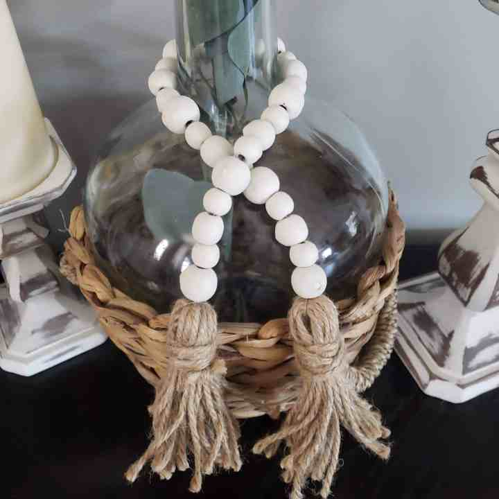 Farmhouse Wooden Bead Garland wrapped around a glass vase