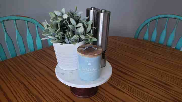A cake stand holding a plant, candle and salt and pepper for a kitchen table centerpiece blog post