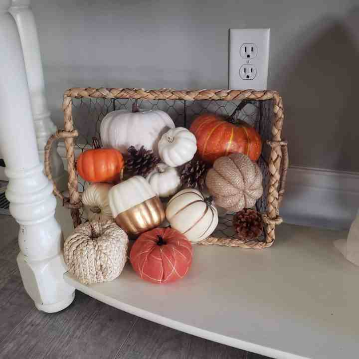 Basket of pumpkins spilling over for simple fall entryway look