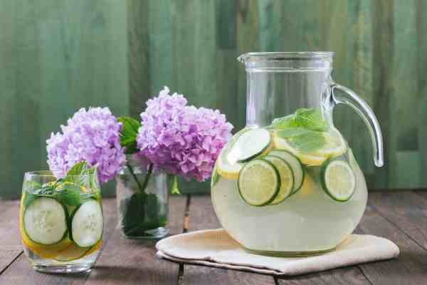 glass pitcher of water with lime slices on a table with purple hydrangias in a vase