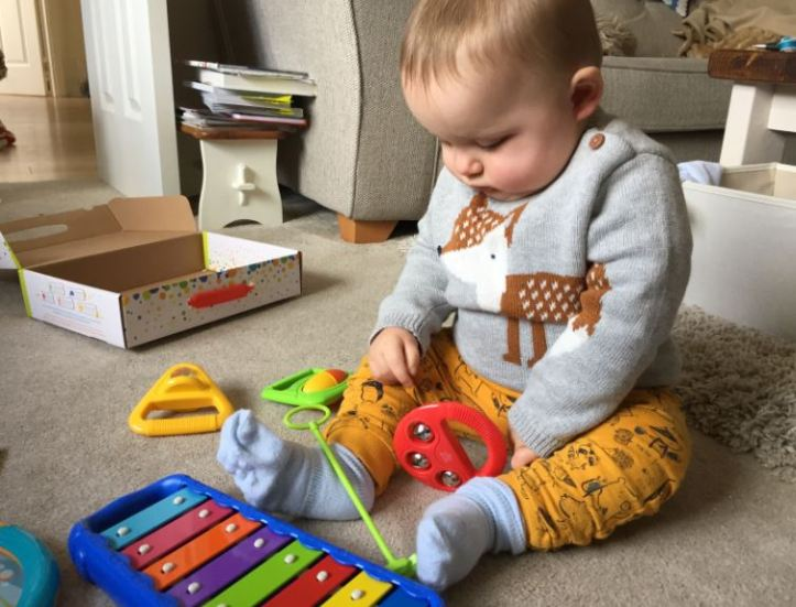 Halilit Toddler Music Orchestra - baby exploring box of musical instrument toys