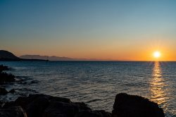 Watching the sunset from the rocky coastline of Cefalu Italy