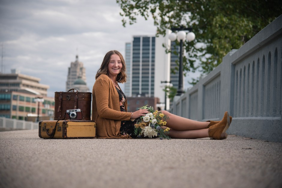 senior girl sitting on bridge, downtown skyline, vintage suitcases, senior girl, senior photography, Babs Mullinax, me and grace, me & grace, Fort Wayne photographer, photo gifts, lifestyle photography, family photos, ideas for family photos, indoor photography, fun family photographer, long-distance family