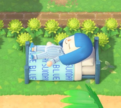 An ACNH person wears blue pyjamas and sleeps on a blue wooden bed
