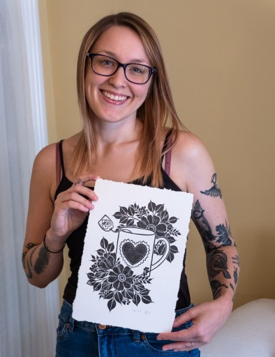 A picture of Alex Flower smiling and holding a print of a mug with a heart on it surrounded by flowers