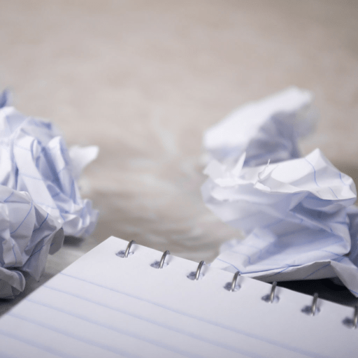 A notepad with two pieces of paper torn off it and scrunched up