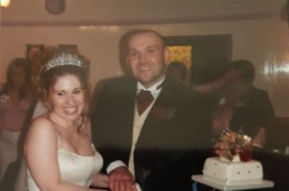 A photo of a married couple standing behind a wedding cake