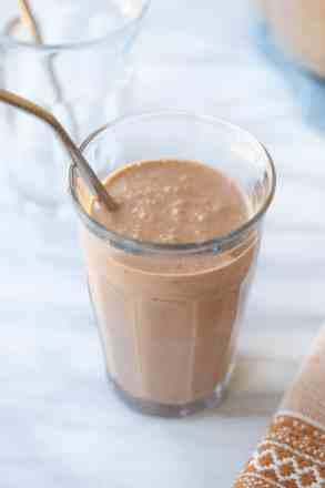 chocolate peanut butter banana smoothie in a glass with a straw