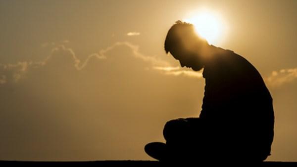 Depressed man set against afternoon sky