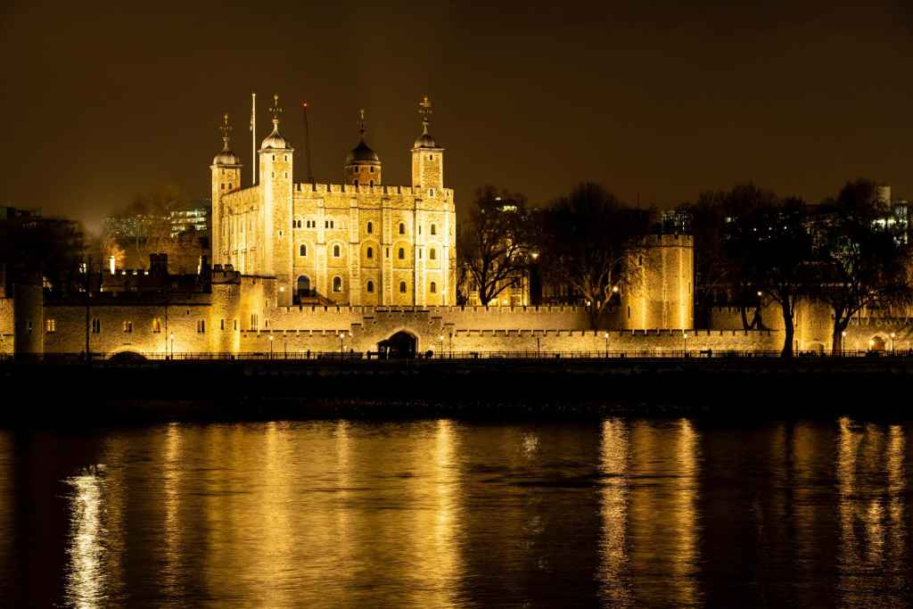 The White Tower and the southern outer wall of the TOwer of London lit up at night and reflected in the Thames River