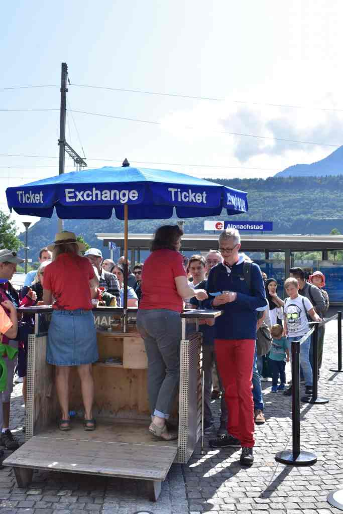 Blue ticket exchange umbrella protects pilatus bahn workers as they work with customers