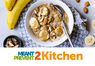 bowl of oatmeal with bananas and almonds on grey cloth