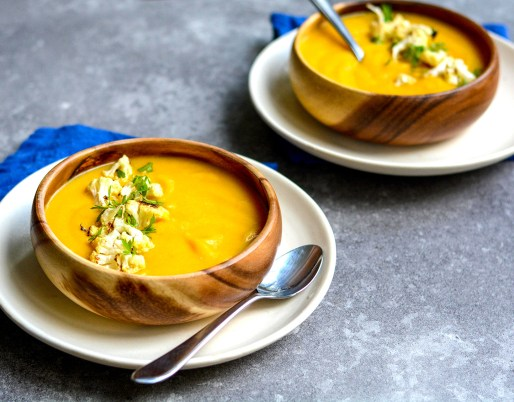 Cauliflower carrot soup with blue napkins in wooden bowls