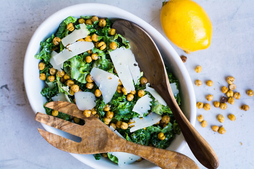 kale salad in bowl with lemon and cheese