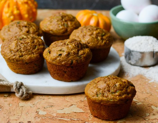 muffins on a table with flour and pumpkin