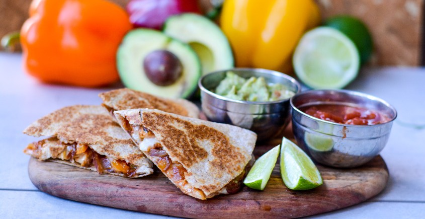 quesadillas on board with veggies in background