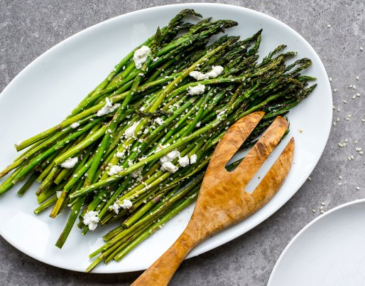 white plate with roasted asparagus and goat cheese