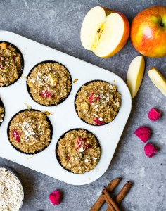 baked oatmeal cups in muffin tray with raspberries and apples top view