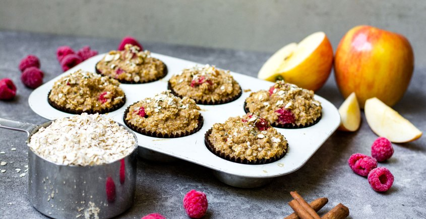 baked oatmeal cups in muffin tray with raspberries and apples