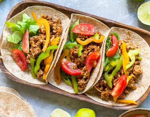ground chicken tacos with limes on wooden plate