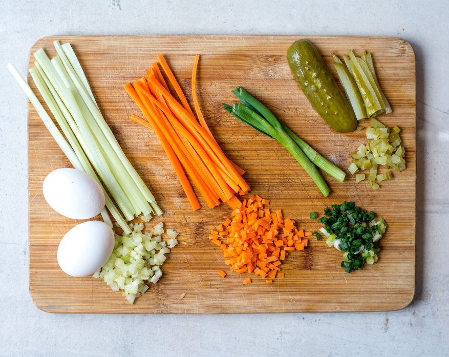 cut up veggies on wooden cutting board with eggs