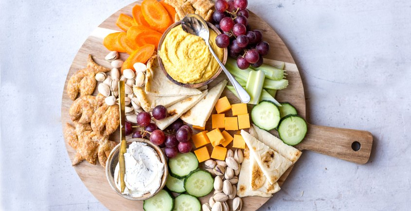 Snack platter on wooden board with crackers, dips, and veggies