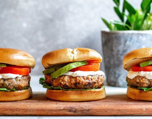 chicken burgers in a row on a wooden board