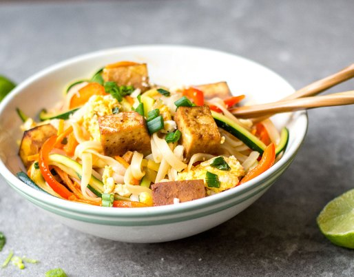 Pad thai in bowl with limes