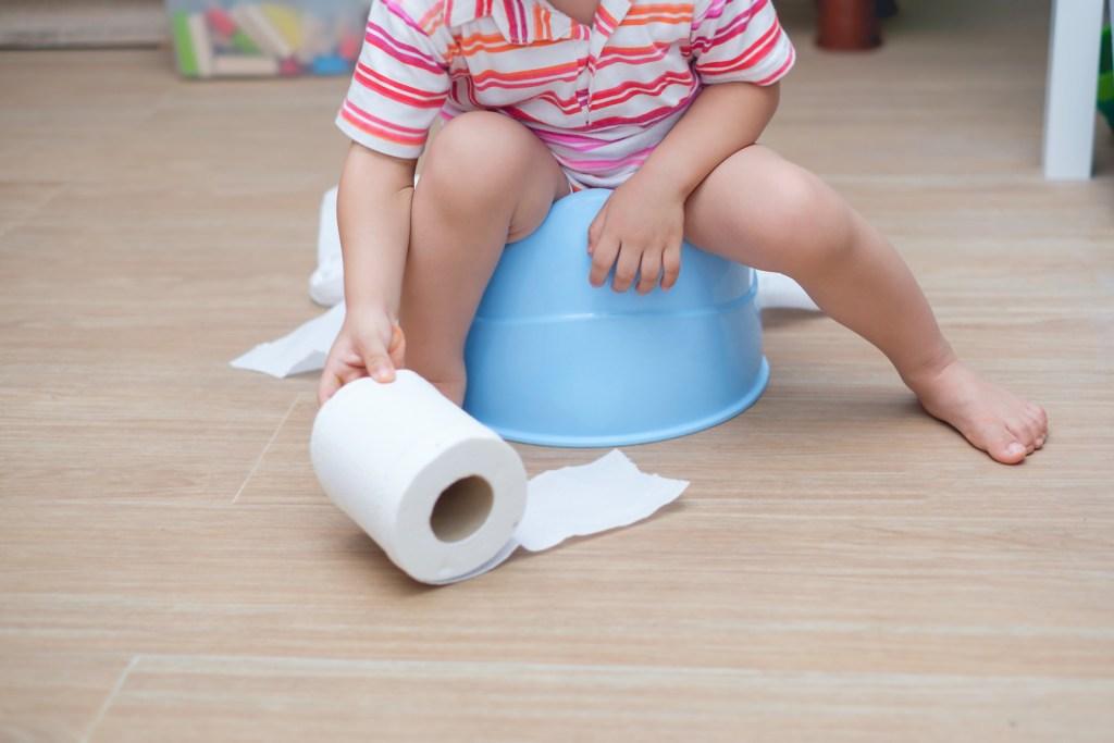 toddler-boy-sitting-on-blue-potty-holding-toilet-paper