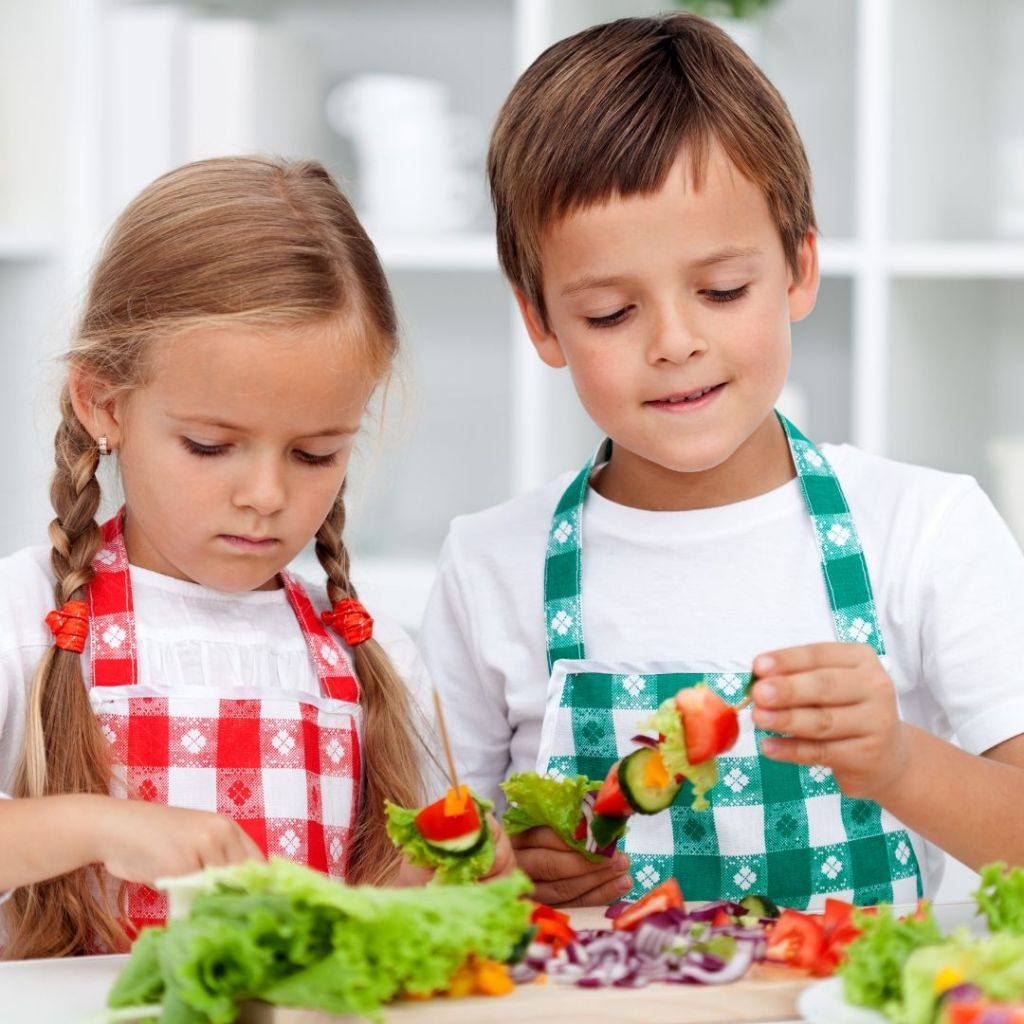 girl-and-boy-wearing-aprons-next-to-each-other-in-kitchen-making-salad