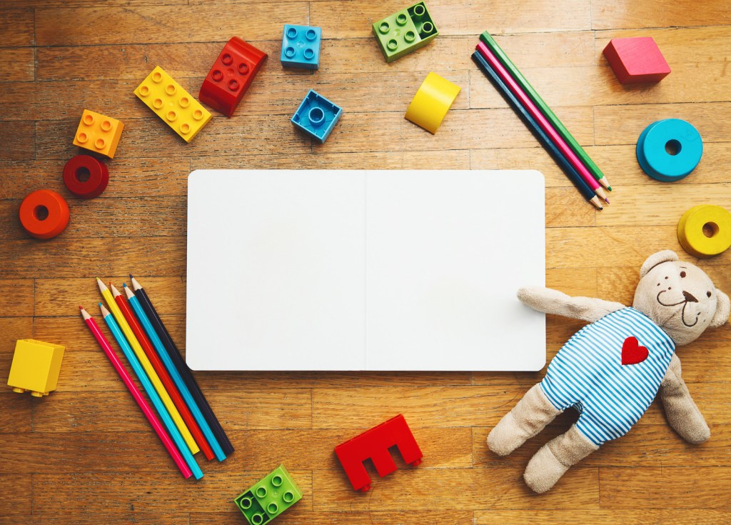 Child-or-baby-play-set-with-empty-book-or-notepad,-toy-wooden-blocks-plastic-constructor-colored-pencils-teddy bear-Back-to-school-education-concept-Kindergarten--or-preschool-background.