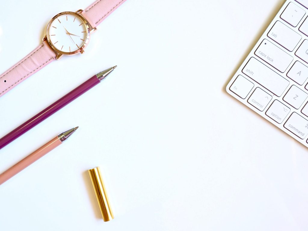round-gold-colored-watch-and-two-pens
