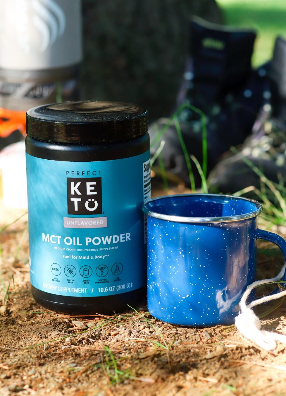keto coffee creamer and an enamel camping cup with some hiking boots and a camp stove