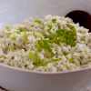 a bowl of coconut cauliflower rice with parsley and a serving spoon
