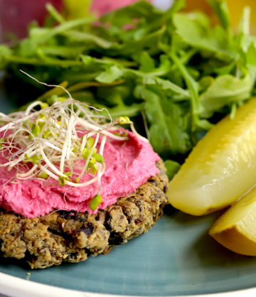 a vegan keto mushroom burger with beet hummus, broccoli sprouts, pickles and arugula salad