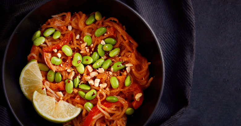 a bowl of shirataki noodles in a thai red curry sauce with lime, peanuts and edamame