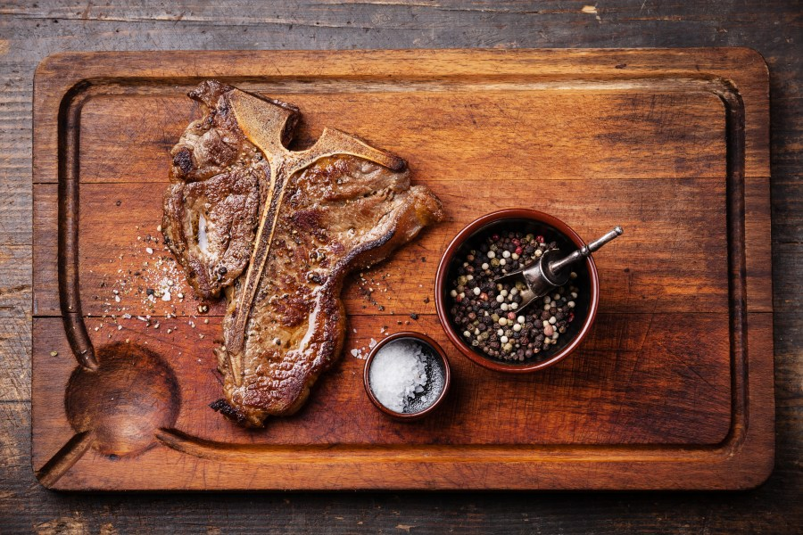Grilled T-Bone Steak with salt and pepper  on meat cutting board