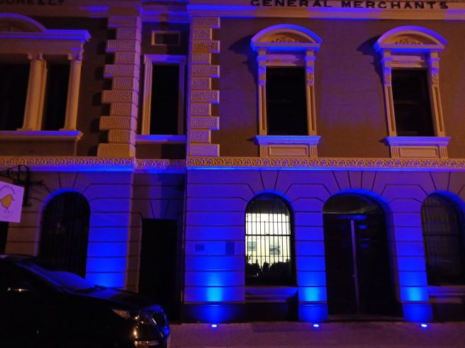 Moores building facade lit in blue