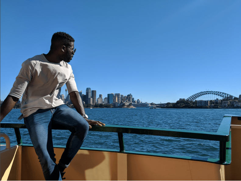 Fane Mensah leaning on a railing on a ferry on Sydney Harbour with the Harbour Bridge in the background