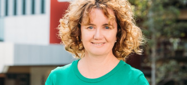 Professor Sonya Marshall-Gradisnik standing outside a Griffith University building wearing a green top.