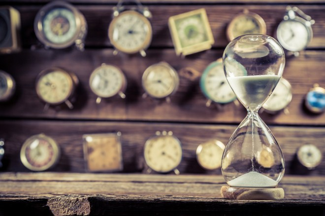 Old hourglass on the background of clocks