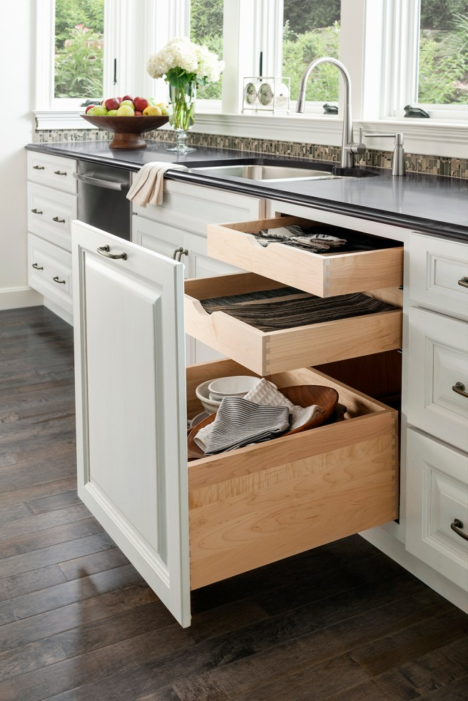 This full-height pull-out conceals a series of drawers for maximizing storage while complementing the dishwasher's single door panel.