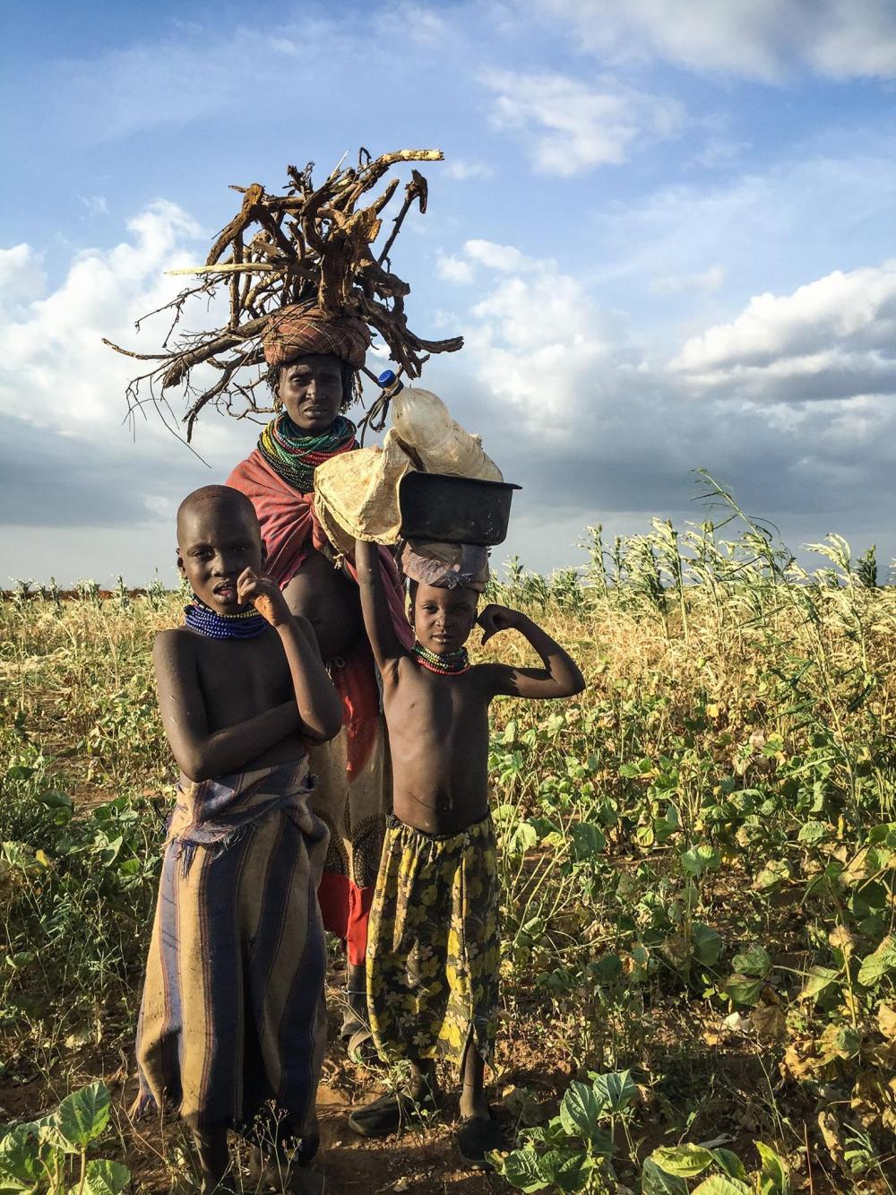 After a long day working in the fields, a woman and her children return home carrying firewood and cooking utensils. Kakuta, Nyangatom, lower Omo, May 2016.