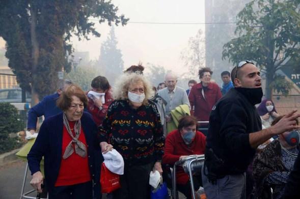 Emergency workers evacuate the elderly. The Guardian/Photo: Baz Ratner/Reuters