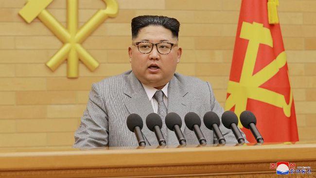 Pencitraan Kim Jong-un dengan Jas Warna Terang Kim Jong-un mengenakan jas abu-abu saat menyampaikan pidatonya. Analis menyebut pilihan itu untuk menunjukkan citra lebih santai. (KCNA/via REUTERS)