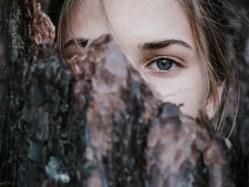 understanding introverts - calm woman behind tree bark in park