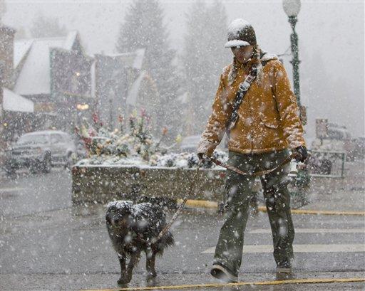 Ali Fuchs, de Crested Butte, Colorado, camina con su perra Bella durante una nevada el lunes 21 de septiembre de 2009. (Foto AP/Nathan Bilow)