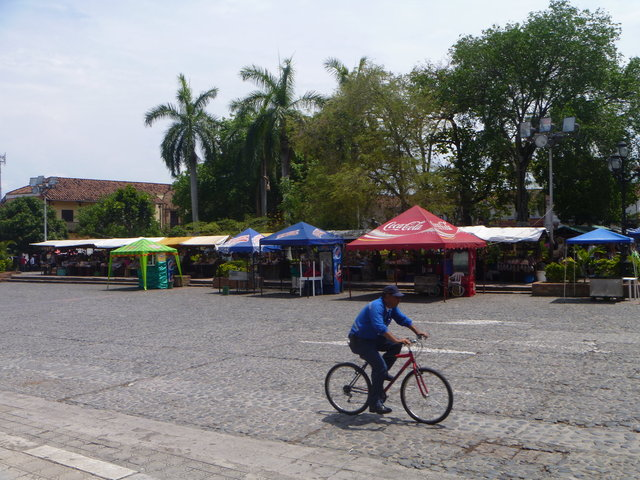 As he rides by, behind him, the Saturday market in Santa Fé de Antioquia is almost ready for business.