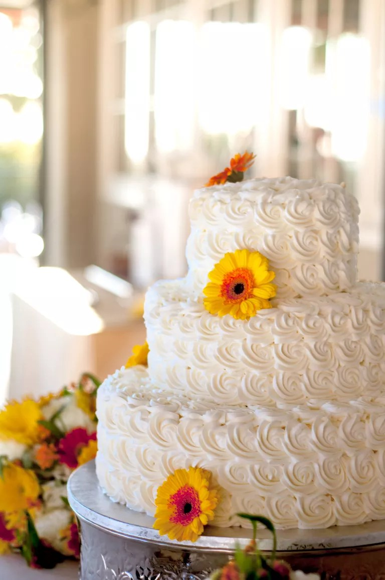 7 Beautiful Buttercream Frosted Wedding Cakes White buttercream wedding cake with gerbera daisies and white rosettes