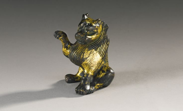 A rare gilt-bronze figure of a seated winged lion, 6th-7th century